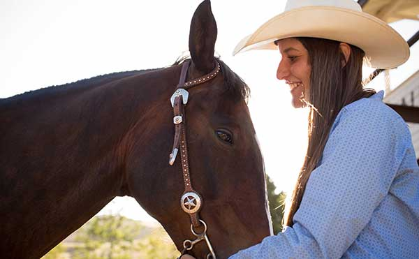 A cowgirl and a beautiful brown horse in bridle