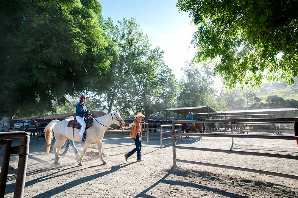 Wrangler leading a horse and rider into the corral at the Alisal Barn