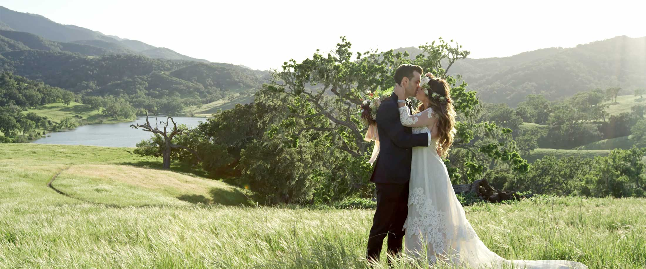 Happy couple just married and kissing at Alisal Lake at the Alisal Guest Ranch