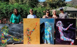 Four women wranglers showing off their paintings.