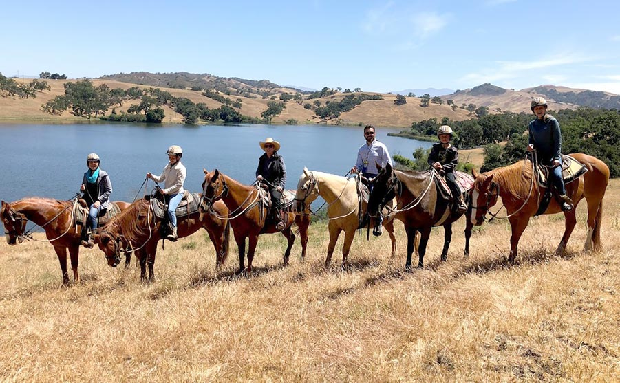 A family on horses out on a ride by Alisal Lake