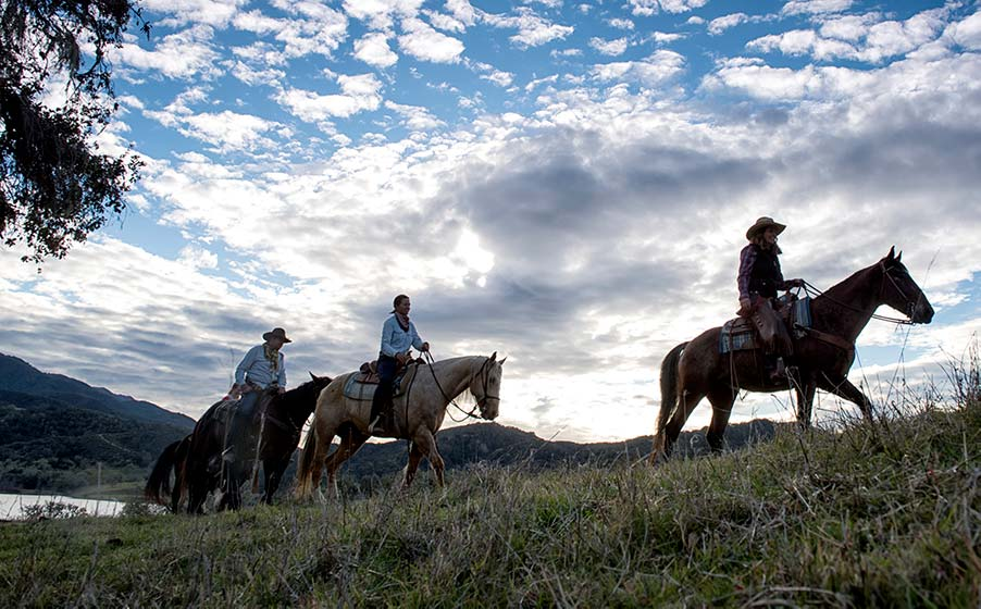 A horseback ride with a beautiful cloudy sky behind