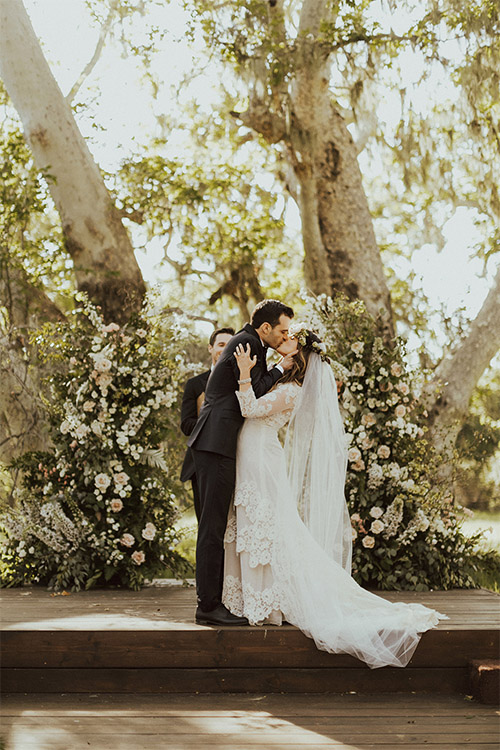A bride and a groom kissing under the sycamore trees at a beautiful, rustic wedding at The Alisal