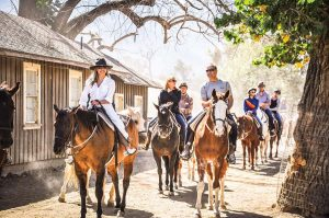 Riders on horseback at the Alisal entering the barn area after a ride on a sunny day