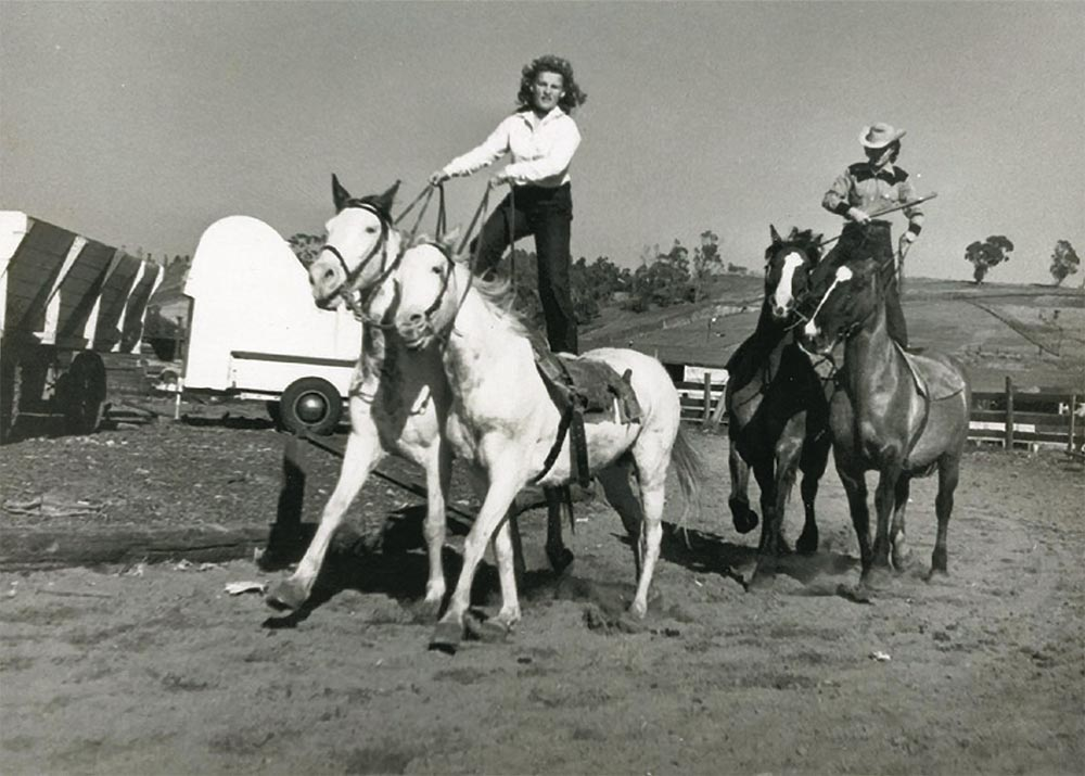 Cowgirl Audrey Griffin riding two horses at one time standing on the saddles