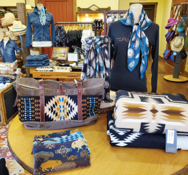 Purses, shirts, hats, and blankets on a table at the Alisal Mercantile store