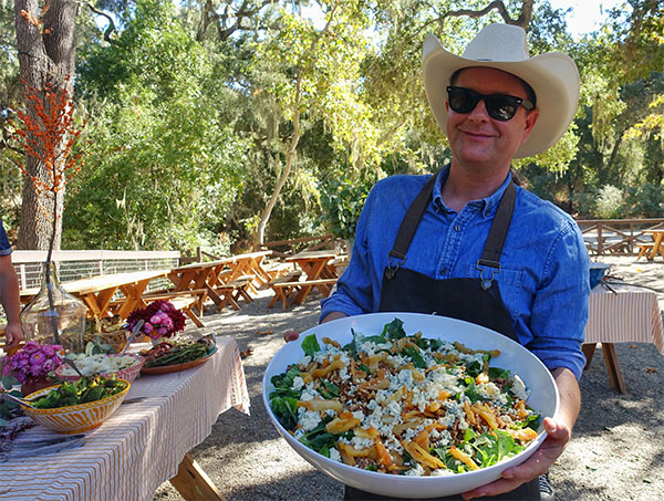 A chef in a cowboy hat and sunglasses holding out a beautiful summer salad at the Alisal Guest Ranch & Resort