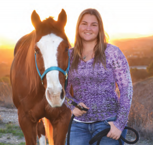 Alisal wrangler Beth Field posing next to a horse