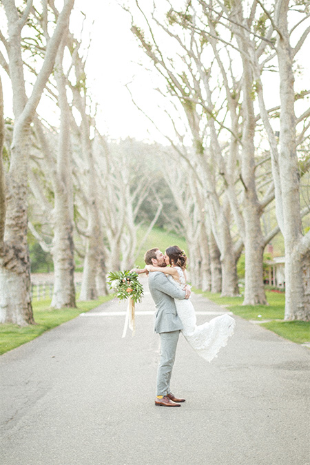 Bride and groom kissing on the main drive at the Alisal Guest Ranch & Resort
