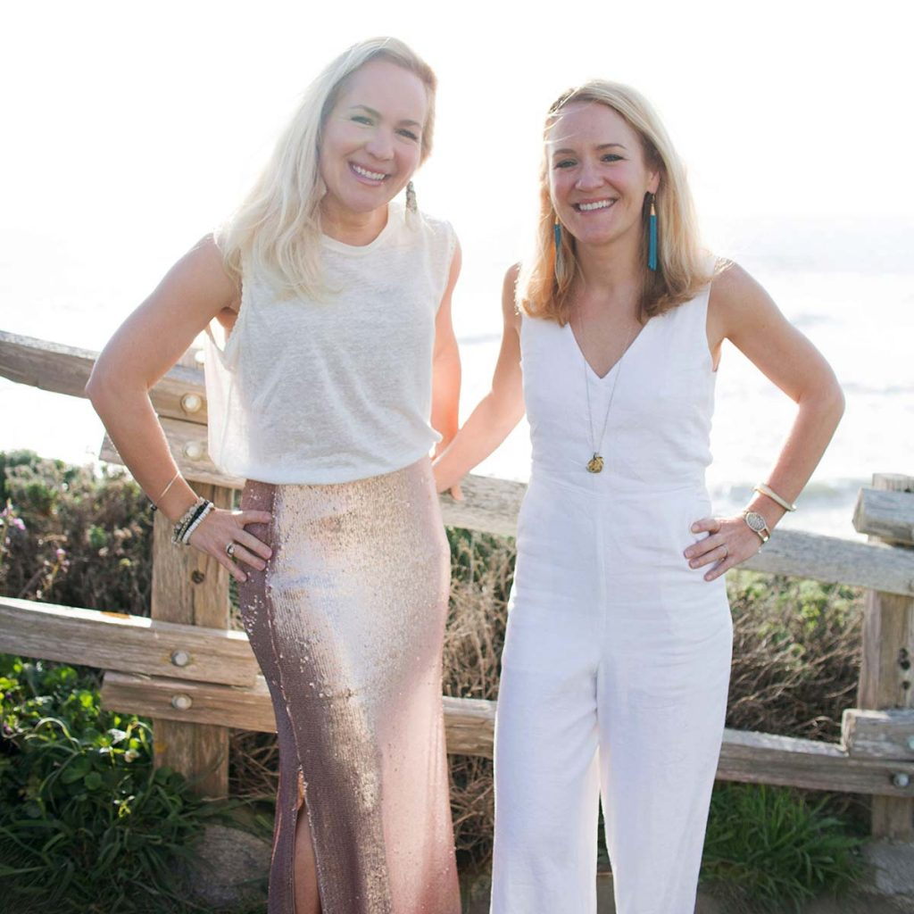 The Firestone Sisters, Mary & Lucy, standing on a walkway overlooking the Pacific Ocean