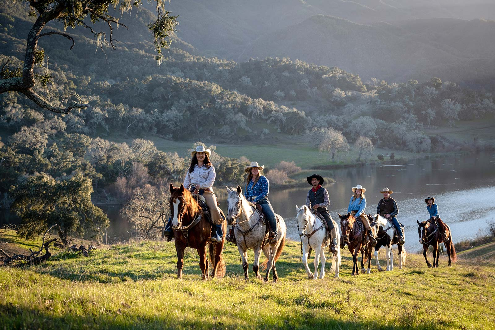 Horseback riders riding over the grassy hill above Alisal Lake