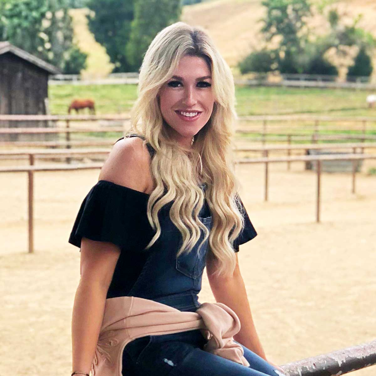 Kelly Cahoon sitting on the corral fence at the Alisal before her horseback ride
