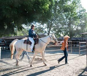 A wrangler at the Alisal leading a horse through the barn area